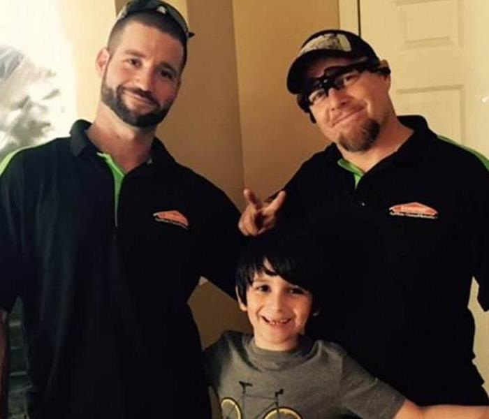 Two of our technicians with a homeowners proud son